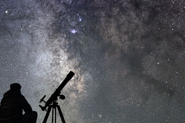 Man beside a telescope looking at the sky