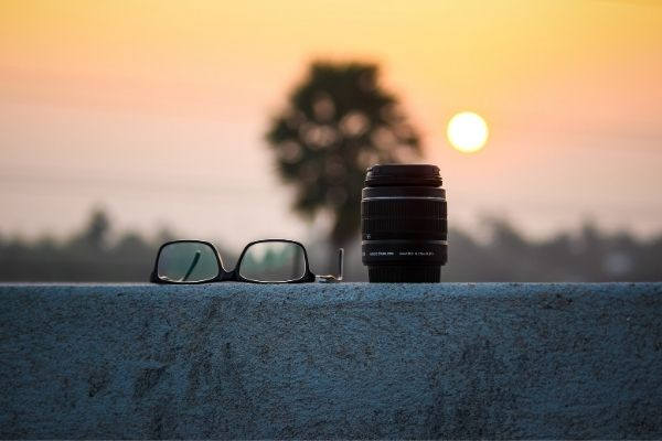 Lens for astrophotography and eyeglasses with the sun in the background