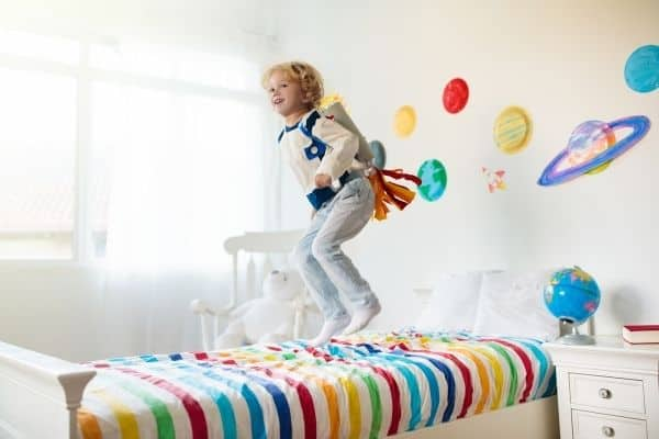 Child in astronomy themed bedroom