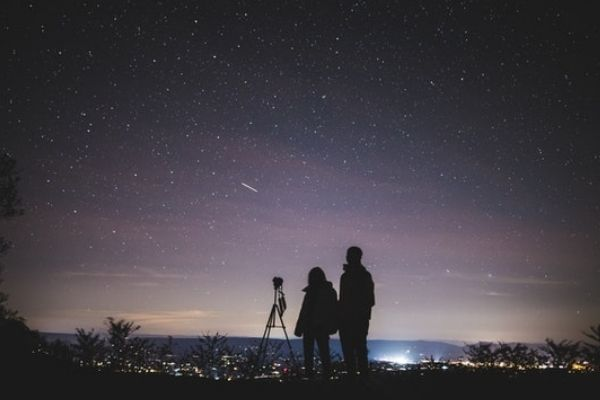 Two people near DSLR camera for astrophotography
