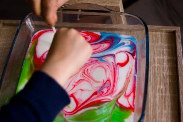 Kid doing science experiment with liquid and colors