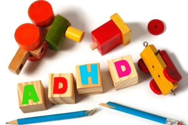 Toys, broken pencil and wooden letter blocks showing ADHD letters