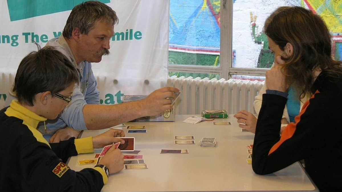 People playing a small box board game