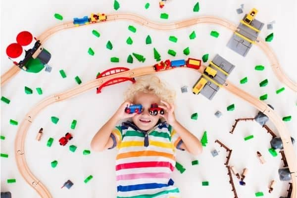 Child holding colorful train toys while lying between railway set