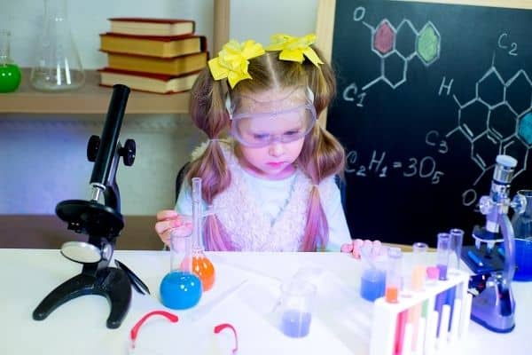 Kid staring at chemistry set on table