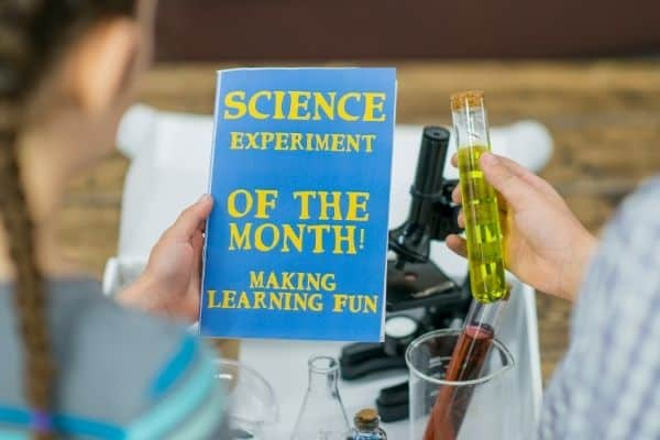 Kids holding science experiment book with microscope and beakers on the table