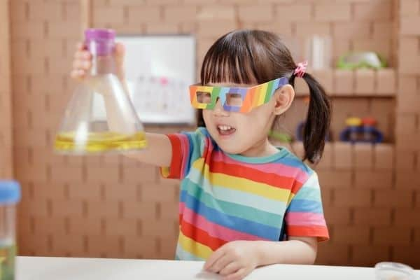 Toddler holding toy beaker for science experiment