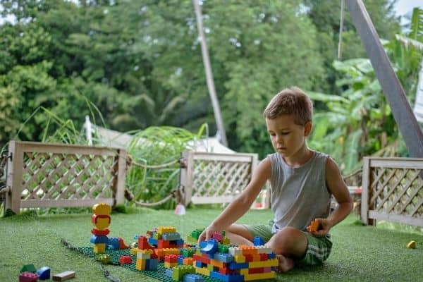 Young boy playing with construction toys outdoors