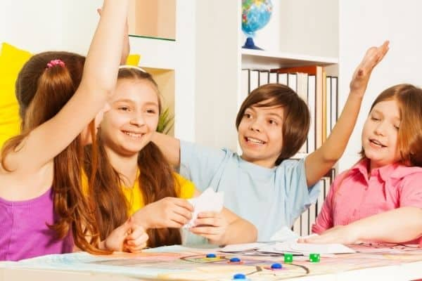 Children smiling and raising hands while playing tabletop game