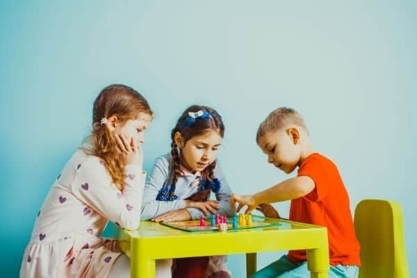 Kids playing board game on green table