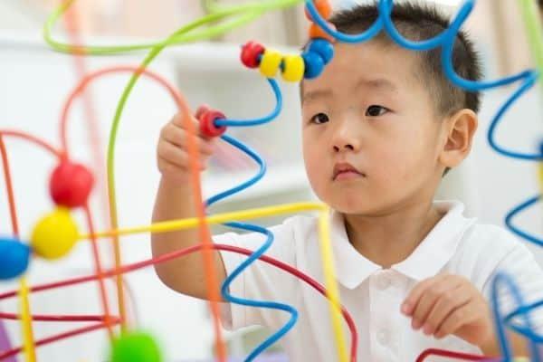 Young boy playing with colorful educational toy