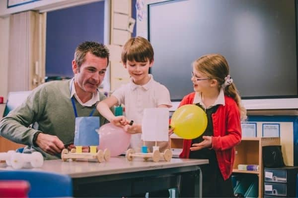 Teacher and young students doing stem activity in the classroom