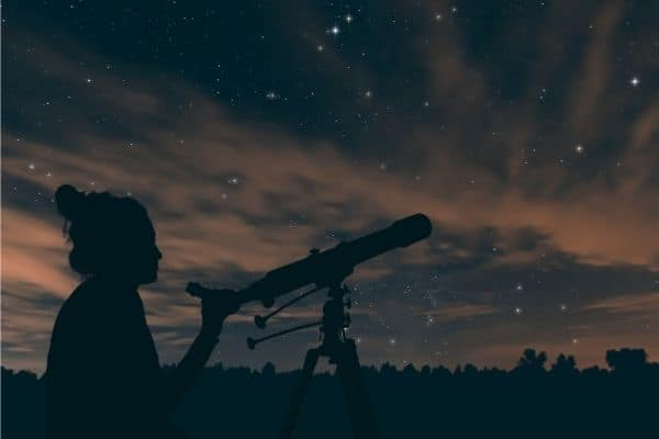 Person using telescope to view stars at night