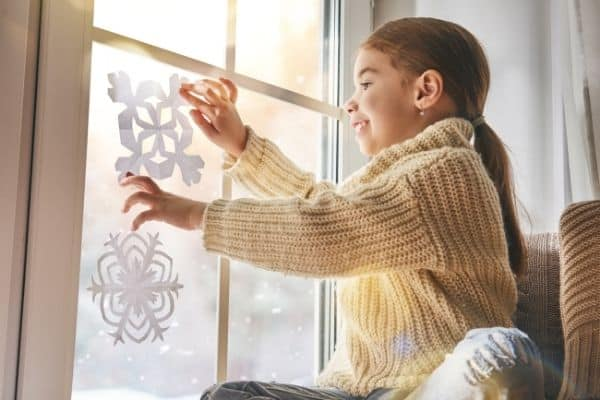 Child sticking paper snowflakes by the window on a snowy day